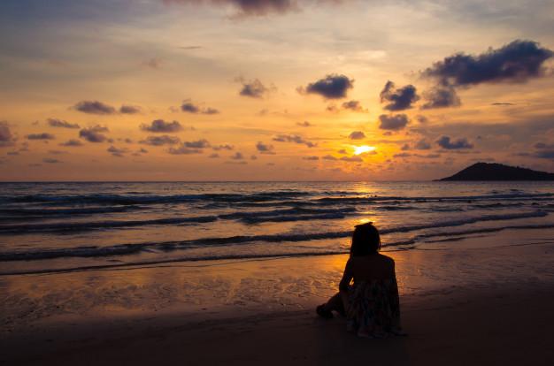 silhouette-girl-sitting-beach-with-sunset_45463-521.jpg